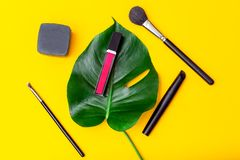 Lip gloss and makeup brush on yellow background. Flat lay. Lip gloss and makeup brush on yellow background. Top view stock photography