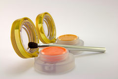Lip Pots with Brush. Two lip pots with lids open and brush on a plain background Royalty Free Stock Photography