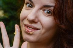 Lip scrub. Redhead model using a homemade lip scrub made out of honey, sugar and olive oil Royalty Free Stock Image