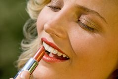 Lip Stick. Young attractive woman doing her make-up royalty free stock photography