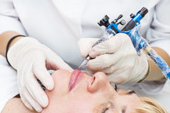 Lip tattoo process. Lip tattoo women in a beauty salon process stock image