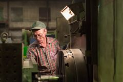 The turner processes the metal part on a mechanical lathe. royalty free stock image