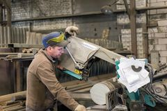 The worker makes the sawing of the metal workpiece on a band saw. stock image