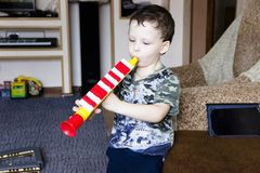Portrait of cute little boy playing flute in toy stock photos