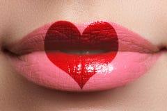在嘴唇的心脏亲吻 有心脏形状油漆的秀丽性感的充分的嘴唇 红色上升了 美丽组成 唇膏和Lipgloss 库存图片
