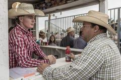 LIPIEC 22, 2017 NORWOOD KOLORADO - kowboje przy koncesja stojakiem przy San Miguel Basenowym rodeo, San Miguel Byk, Kolorado fotografia stock