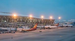 15 Lipiec, 2018 Pudong lotnisko, Szanghaj, Chiny Nowożytni pasażerscy samoloty parkowali śmiertelnie budynku brama przy zdjęcia stock