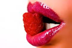 Lippen met een framboos Stock Afbeeldingen