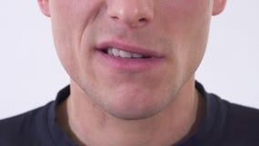 Lippen und Kinn des Mannes, die Ärger und Selbst zeigen, stellten Grinsen zufrieden Schießen auf einem weißen Hintergrund stock footage