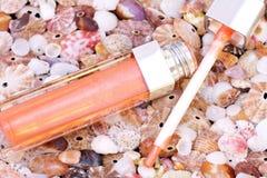 Lippenglanzgefäß auf Seashellshintergrund Lizenzfreie Stockfotografie