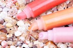 Lippenglanzgefäße auf Cockleshellhintergrund Lizenzfreie Stockbilder