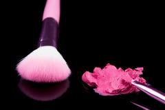 Lippenstift mit einem Bürstenmake-up auf Schwarzem Lizenzfreies Stockfoto