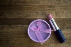 Lippenstift und Geschenkbox auf einem hölzernen Hintergrund Stockbilder