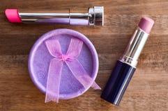 Lippenstift und Geschenkbox auf einem hölzernen Hintergrund Stockfotos
