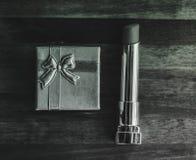 Lippenstift und Geschenkbox auf einem hölzernen Hintergrund Stockbild