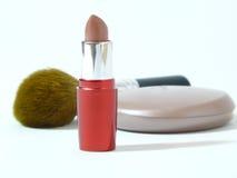 Lippenstift- und Puderpinsel auf einem weißen Hintergrund Stockbilder
