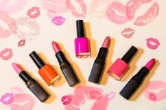 Lippenstifte und Nagellacke auf beige Hintergrund Stockfotografie