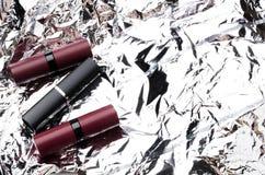 Lippenstiftrohre auf glänzender Oberfläche, leerer Raum stockbild