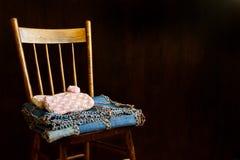 Lippers und Steppdecke falteten sich ordentlich auf dem Stuhl der Großmutter lizenzfreies stockbild