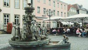 Lippstadt/Alemanha - em julho de 2019: Fonte no centro da cidade de Lippstadt no mercado com o restaurante no fundo filme