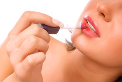 Lips. Girl is painting lips with pink lipstick on the white background Royalty Free Stock Images