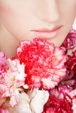 Lips and flowers. Close-up shot of woman's lips and the bunch of colorful flowers Royalty Free Stock Images