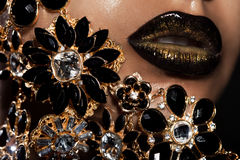 Lips with golden jewelry. Female lips with golden jewelry Royalty Free Stock Photos