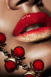 Lips with golden jewelry Royalty Free Stock Photos