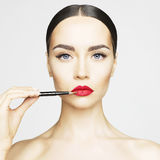 Lips makeup. Studio fashion photo of beautiful young lady applied lipstick.  Perfect face makeup Stock Images
