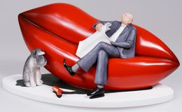 Lips sofa. Photo of a statuette. The man is sitting on the lips-shaped sofa Stock Image