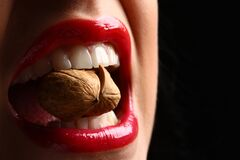 Free Lips, Teeth, Nut Cracking. Woman Red Lips Eating Tasty Food. Woman Cracking A Nut With Her White Teeth Stock Photo - 169629010