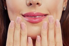 Lips with trendy color glossy lipgloss makeup. Beautiful female mouth and perfect manicured nails.  stock photography