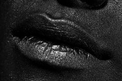 The lips of a young girl. Covered with black paint Stock Photo