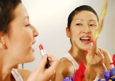 Lipstick. Pretty Asian Girl Putting on Lipstick.  (Focus on mirror image Royalty Free Stock Photos