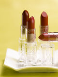 Lipstick. Tubes of lipstick on a white tray with a yellow background stock images