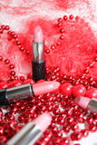 Lipstick. It is decorated by a red beads Stock Photography