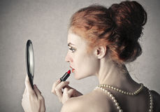 Lipstick. A beautiful woman is putting lipstick on her face royalty free stock images