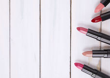 Lipstick Border. Lipsticks on a distressed wood background Royalty Free Stock Photography