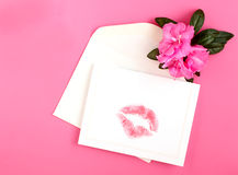 Lipstick on card. Red lipstick pressed on card and envelope surrounded by pink azalea flower on white background symbolic of love for Valentine's Day Royalty Free Stock Photos