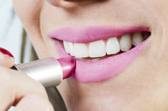 Lipstick. Close up of a beautiful female applying pink lipstick, white background Stock Images