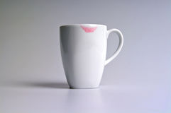 Lipstick and Coffee. White coffee cup with womens red lipstick mark on the rim royalty free stock photos