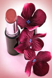 Lipstick and crimson flowers Royalty Free Stock Photos