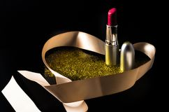 Lipstick with heart-shaped ribbon and golden specks of glitter dust. Fancy and glamour photograph of a lipstick with ribbon and golden specks of glitter dust on Royalty Free Stock Photography