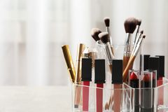 Lipstick holder with different makeup products on table indoors, closeup. Space for text stock photo