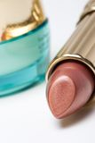 Lipstick and jar of face cream. Closeup of fresh lipstick and a container of cosmetic face cream on white backround stock images