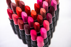Lipstick love. Collection of lipsticks arranged into the shape of a heart Royalty Free Stock Photos