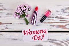 Lipstick, nail polish and flowers. Stock Photo