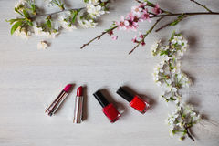 Lipstick and nail polish purple and red flowers. Tools for creating a flirtatious and attractive image. Persistent cosmetic products for painting. Cosmetics royalty free stock photo