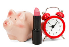 Lipstick with piggy bank and alarm clock Royalty Free Stock Image