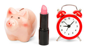 Lipstick with piggy bank on white. Lipstick with piggy bank and alarm clock on isolated white background Stock Photos